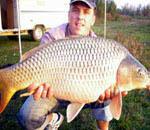 Un pescar fericit si un peste frumos perins pe lacul Darvari.